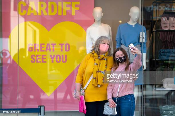 Two women pose for a photograph in the queue for a Primark store as non-essential retail reopens on April 12, 2021 in Cardiff, Wales. Lockdown...