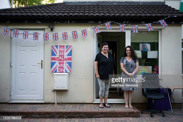 Two women pose for a picture in front of their decorated house on May 08 2020 in Cardiff United Kingdom The UK commemorates the 75th Anniversary of...