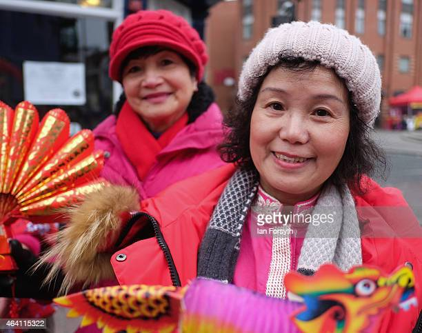 Two women pose for a picture next to a stall selling fans and paper dragons as the Chinese community come together to welcome in the Chinese New Year...