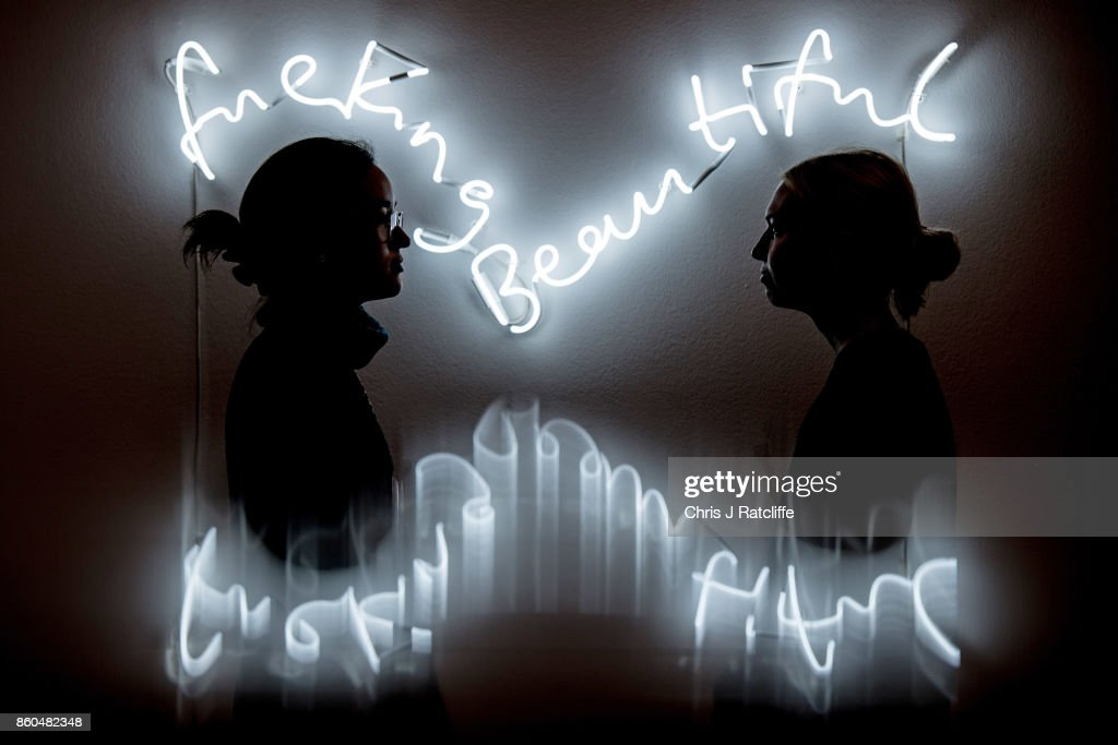 Two women pose for photographs next to fuckingbeautiful by Time Noble and Sue Webster, estimated at £25,000-£35,000, during an Art for Grenfell press call at Sotheby's Art for Grenfell preview on October 12, 2017 in London, United Kingdom. The 'Art for Grenfell' auction will take place on October 16 2017 and includes work by contemporary artists.