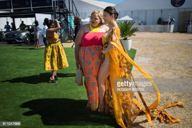 Two women pose for photos as they wait for the start of the Met horse race at Kenilworth race track on January 27 in Cape Town The Met is one of...