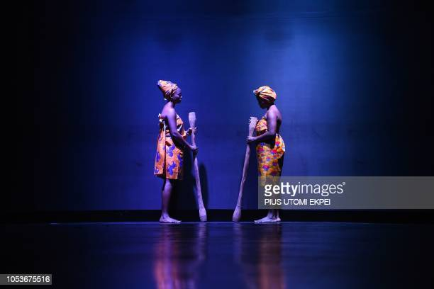 Two women pose holding pestles for pounding yam to form the logo of designer Nack on the runway during the Lagos Fashion Week on October 25 2018...