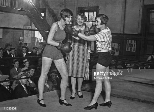 Two women pose in a boxing ring in gloves shorts and high heels circa 1925 The audience is allmale