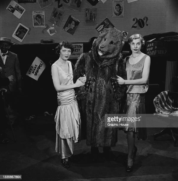 Two women pose one on either side of a person wearing a bear costume at a party, location unspecified, 1955. Covers of 'Theatre Magazine' are...