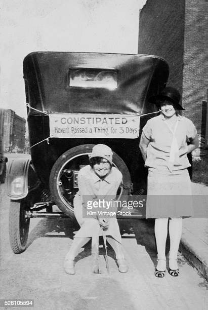 Two women pose with a constipated car ca 1926