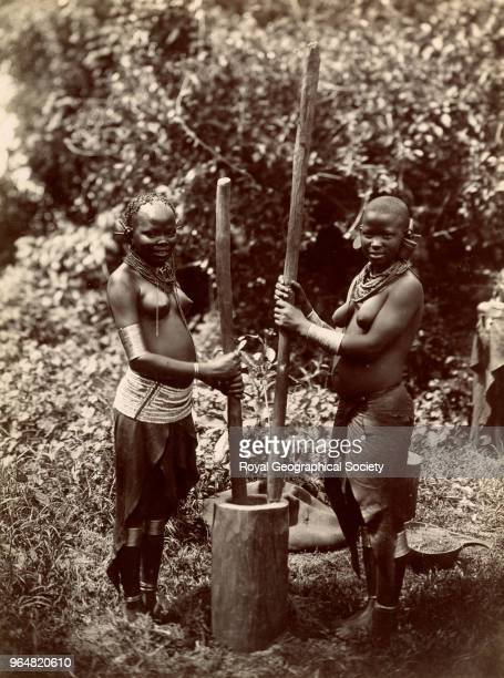 Two women pounding grain in a pestle and mortar Uganda 1911