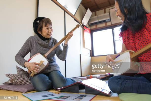 two women practice shamisen - vangen imagens e fotografias de stock