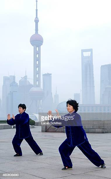 Two women practice the Chinese martial art taichi at dawn on the Bund on February 1 2009 in front of the Oriental Pearl tower and the World Financial...