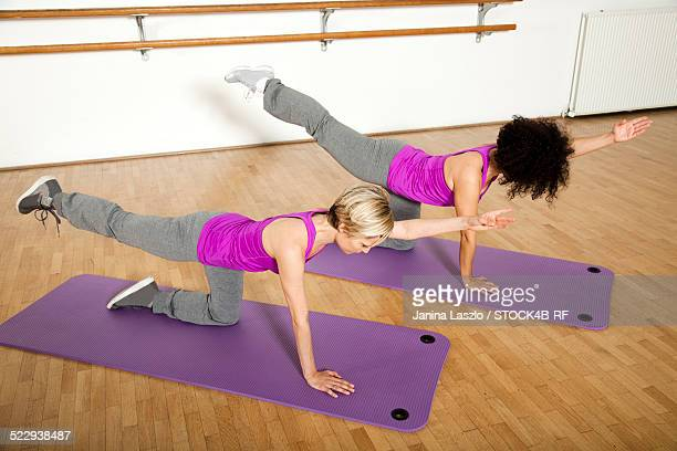 Two women practicing on exercise mats in a health club