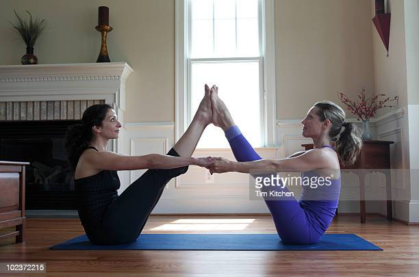 Two women practicing partner yoga in home