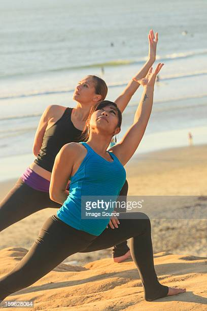 Two women practising yoga on beach