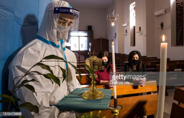 Two women pray in the church Santa Maria delle Grazie in Catania where a mannequin in a protective suit has been placed on the altar holding a...