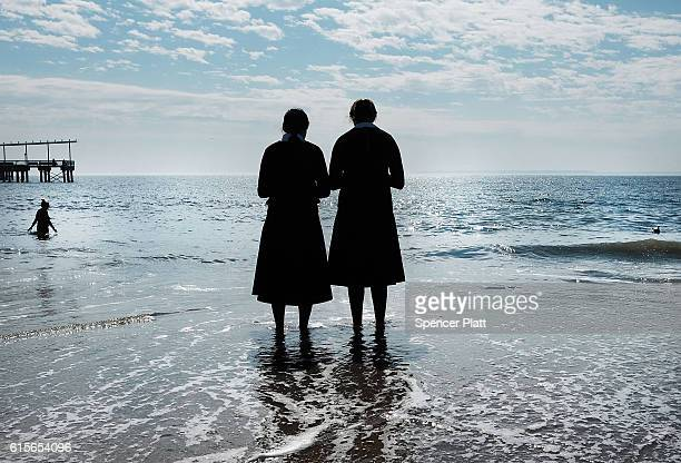Two women pray in the ocean at Coney Island on a warm autumn day on October 19 2016 in New York City New York City and much of the East Coast has...