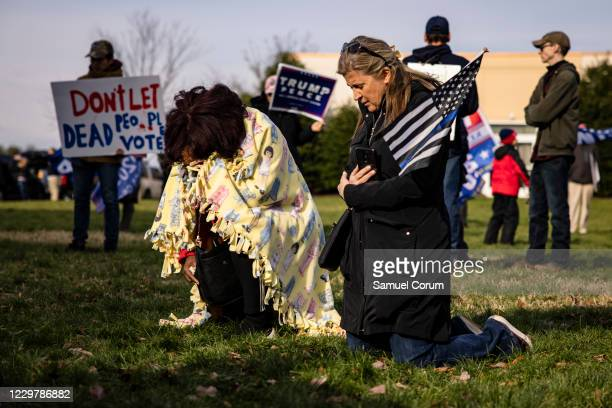 Two women pray on their knees as they gather with other supporters of President Donald Trump, most without masks, outside of the Wyndham Gettysburg...