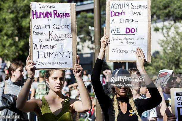 Two women protestors hold banners during a protest demanding that asylum seekers held in off shore detention to be brought to Australia at a rally in...