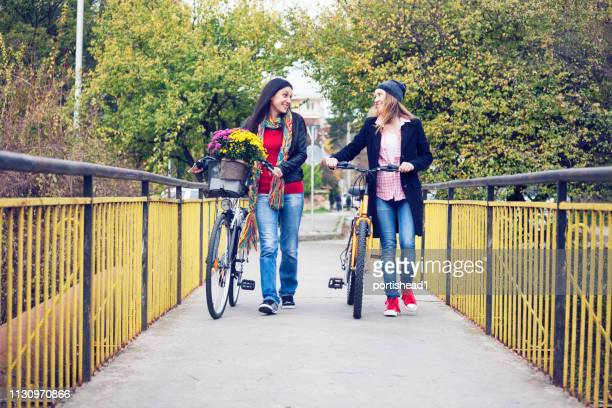 two women pushing bikes and talking - september stock pictures, royalty-free photos & images