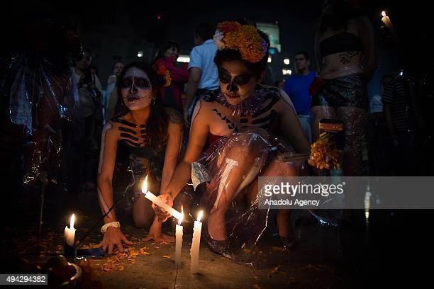 Two women put candles on ground during Procession of the Catrinas in Mexico City Mexico on October 25 2015 The Catrina is a figure of a skeleton...