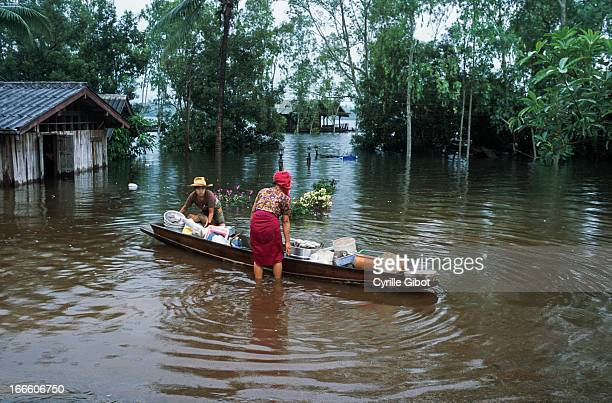 Two women put kitchen utensils on a boat to save them from a flood due to heavy monsoon rains, Kanchanaburi Province, October 2010