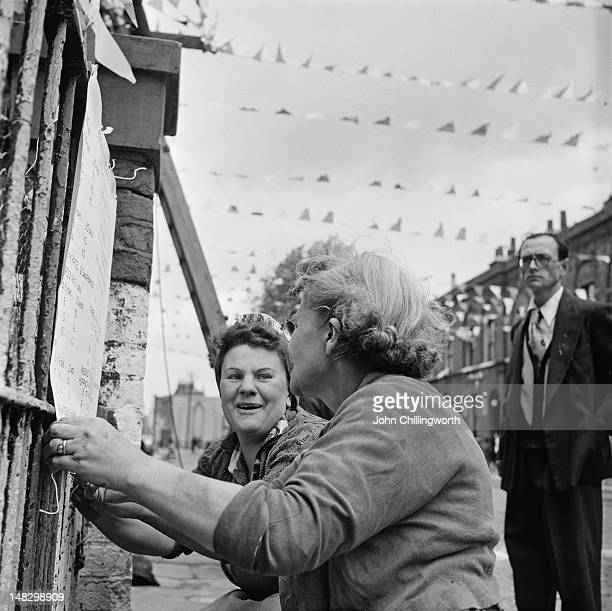 Two women putting up a list of party games and sports activities at a party to celebrate the coronation of Queen Elizabeth II held in Morpeth Street...