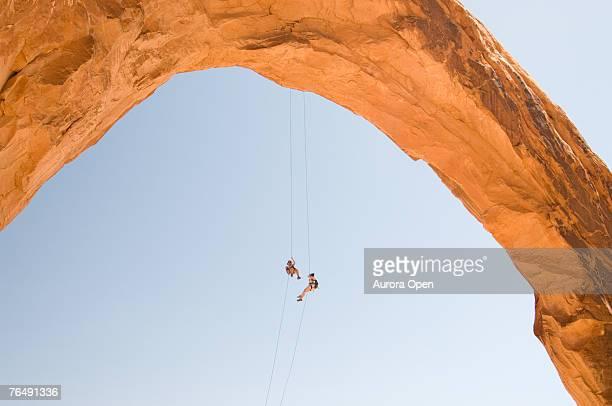 Two women rappelling off an arch in Moab, Utah.