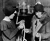 Two women read tickertape in a stock brokers office in st paul 1929 picture id576822352?s=170x170