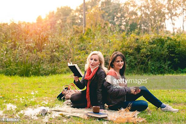 Two women reading book in the park.