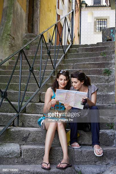 Two Women Reading Road Map on Steps