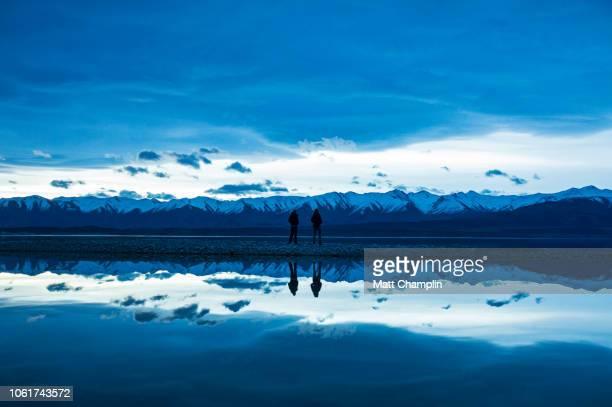 Two Women Reflected in Lake Pukaki at Evening