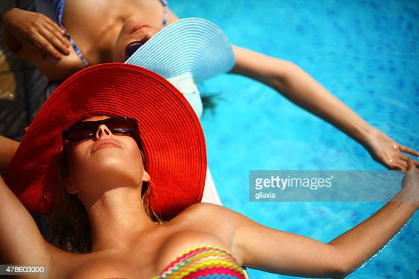 two women relaxing by swimming pool. - women sunbathing stock photos and pictures