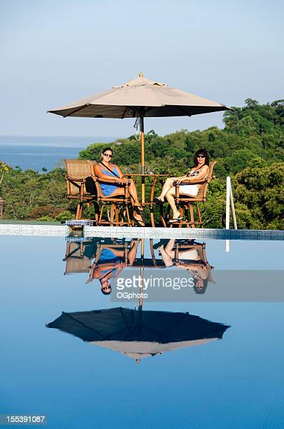 two women relaxing by the pool - ogphoto stock pictures, royalty-free photos & images