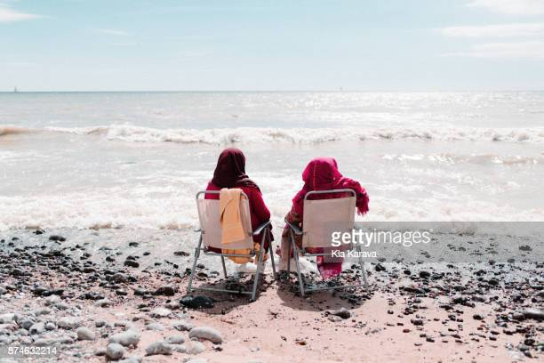 Two Women Relaxing in Chairs on a Beach
