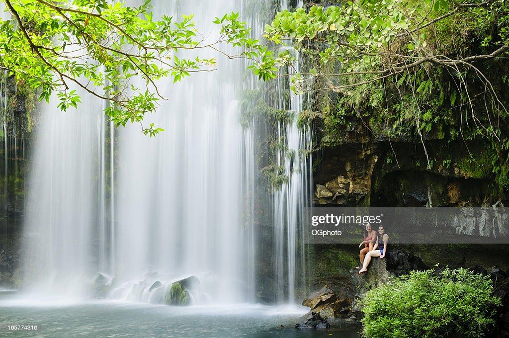 Zwei Frauen entspannen neben einem Wasserfall. : Stock-Foto