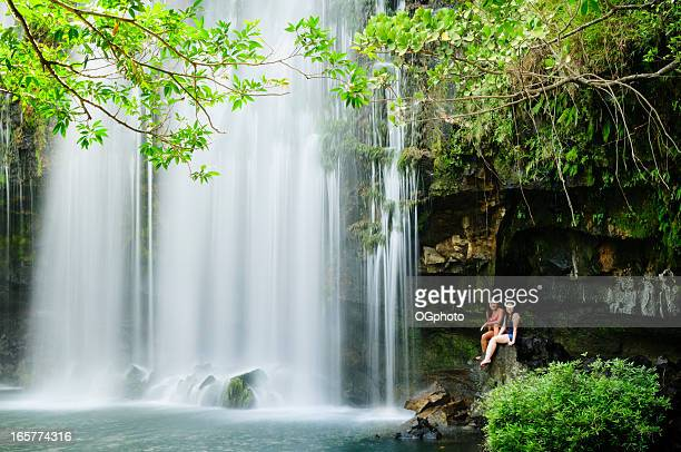 Two women relaxing next to a waterfall.