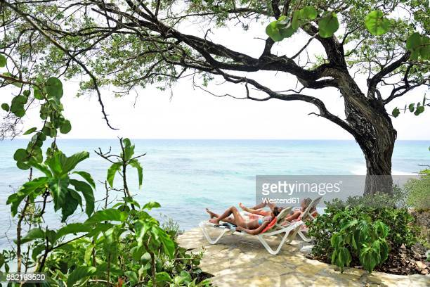 two women relaxing on sun loungers at the sea - women sunbathing stock photos and pictures
