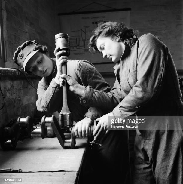 Two women repairing a crankshaft and piston from a large engine at an ATS driving school in the UK during World War II, January 1941. In the...