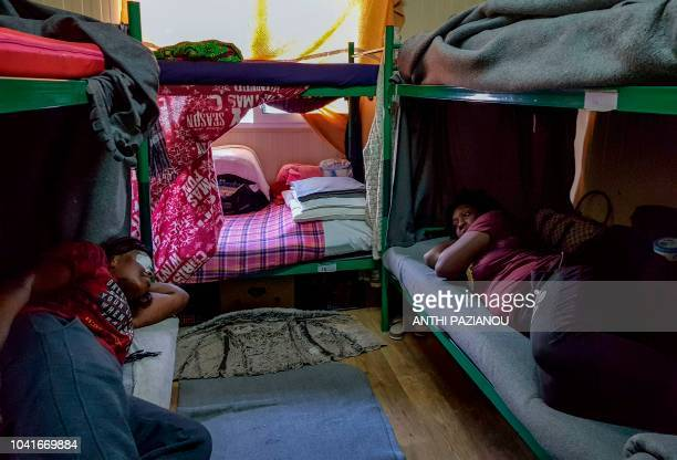 Two women rest inside the refugee camp of Moria in the northern Greek island of Lesbos on September 25 2018 About 20000 refugees and migrants more...
