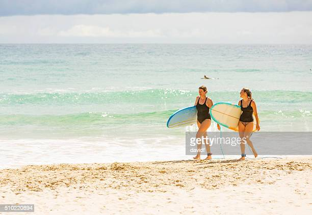 Two Women Returning From Surfing at the Beach