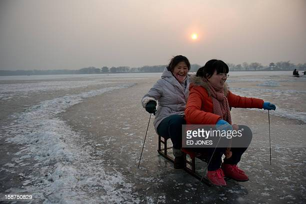 Two women ride a luge on a frozen lake at the Summer Palace in Beijing on December 27 2012 Forecasts were predicting temperatures of around minus 20...