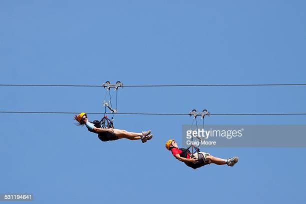 Two women ride a zip line in Whitefish, Montana.