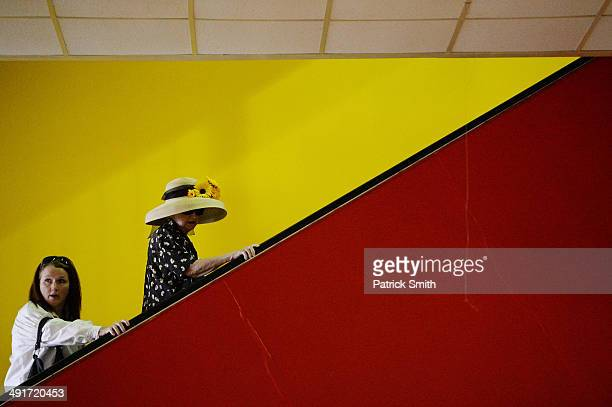 Two women ride an escalator prior to the 139th running of the Preakness Stakes at Pimlico Race Course on May 17 2014 in Baltimore Maryland