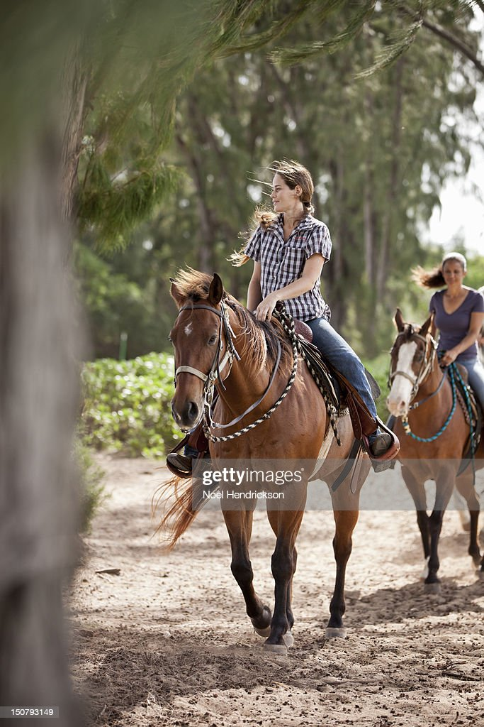 Two women ride horses on a trail : Stock Photo