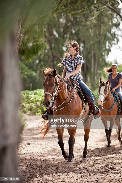 Two women ride horses on a trail
