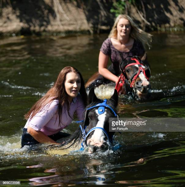 Two women ride their horses through the River Eden on the first day of the Appleby Horse Fair on June 7 2018 in Appleby EnglandThe fair is an annual...
