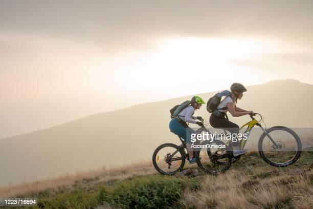 zwei frauen fahren mit elektro-mountainbikes grasbewachsenen hang hinauf - freizeitaktivität im freien stock-fotos und bilder