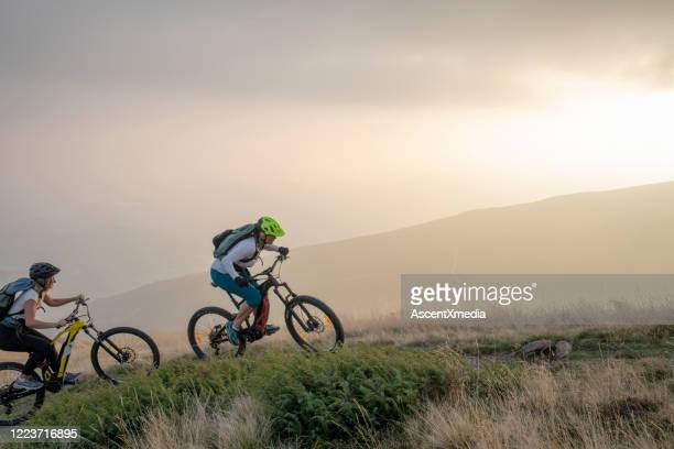 zwei frauen fahren mit elektro-mountainbikes grasbewachsenen hang hinauf - radsport wettbewerb stock-fotos und bilder