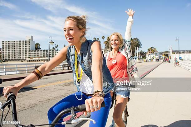 Two women riding a tandem cruiser bike together, Santa Cruz, California, USA