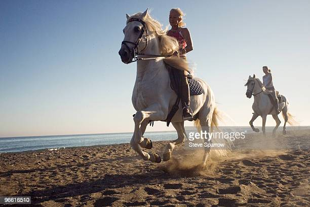 two women riding horses on beach - andare a cavallo foto e immagini stock