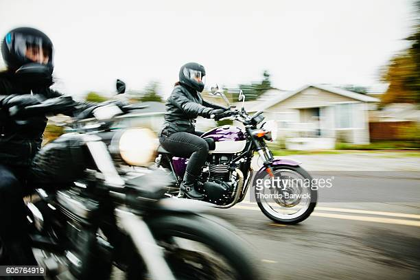 Two women riding motorcycles together on road