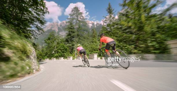 two women riding road bikes on mountain road - road cycling stock pictures, royalty-free photos & images