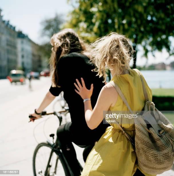 two women riding same bike i city